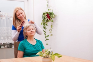 caregiver combing elderly woman's hair