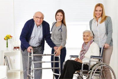 caregivers and elderly couple smiling