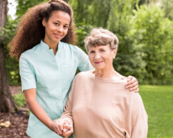 smiling elderly woman and her caregiver